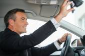 Mature man in formalwear adjusting mirror in car — Stock Photo