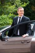 Mature man getting out from car — Stock Photo
