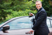 Mature man in formalwear standing near his new car — Stock Photo