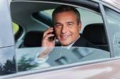 Businessman talking on the mobile phone in car — Stock Photo