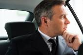 Businessman on the back seat of car — Stock Photo