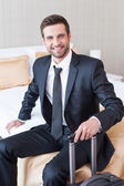 Businessman in formalwear carrying suitcase — Stock Photo