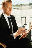 Businessman making notes in airport — Stock Photo