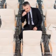Mature man in formalwear in empty conference hall — Stock Photo #52991589