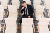 Mature man in formalwear in empty conference hall — Stock Photo