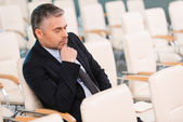 Bored mature man in formalwear in empty conference hall — Foto Stock