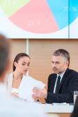 Man and woman in formalwear looking at paper — Stock Photo