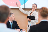 Woman in formalwear pointing projection screen — Stock Photo