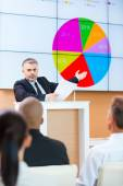 Man in formalwear pointing projection screen — Stock Photo