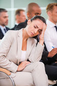 Depressed young woman in conference hall — Stock Photo