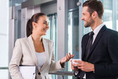 Taking time to chat with colleague. Two cheerful business people discussing something and smiling — Stock Photo