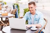 Man working on laptop in cafe — Stock Photo