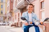 Człowiek jazda skuterem wzdłuż ulicy — Zdjęcie stockowe