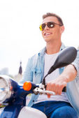 Man in sunglasses riding scooter — Stock Photo