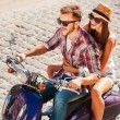 Young couple riding scooter — Stock Photo #54248521