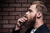 Bearded man smoking a cigarette — Stock Photo