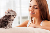 Woman stroking a cute little kitten — Stockfoto