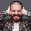 Bearded man covering ears with hands — Stock Photo #54847877