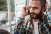 Bearded man expressing negativity while talking on phone — Stock Photo