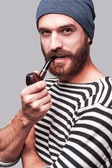Bearded man in striped clothing smoking a pipe — Photo