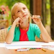 Little girl sitting at the table with colorful pencils — Stock Photo #54916899