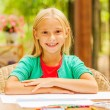 Little girl sitting at the table with colorful pencils — Stock Photo #54916927