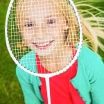 Little girl hiding her face behind badminton racket — Stock Photo #54917017