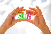 Sun formed from plastic letters in hands — Stock Photo