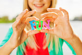Little girl holding colorful plastic letters in hands — Stock Photo