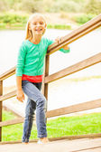 Little girl moving up by  wooden stairs — Stock Photo