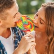 Couple tasting multi colored lollipop — Stock Photo #54926093