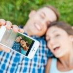 Loving couple making selfie lying on grass. — Stock Photo #54926197