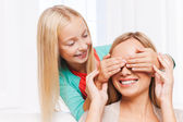 Little girl covering eyes of her cheerful mother — Stockfoto