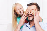 Little girl covering eyes of her cheerful father — Stock Photo