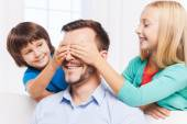 Kids covering eyes of their cheerful father — Stock Photo