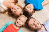 Happy family of four lying on the floor — Stock Photo