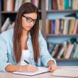 Young woman writing in her note pad — Stock Photo #55321927
