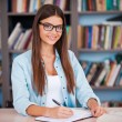 Young woman writing in her note pad — Stock Photo #55321929