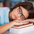 Woman sleeping at the library desk — Stock Photo #55321949