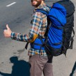 Man carrying backpack stretching thumb up — Stock Photo #55326539