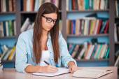 Young woman writing in her note pad — Stock Photo
