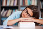 Woman sleeping at the library desk — Stock Photo