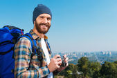 Man carrying backpack and holding camera — Stock Photo