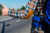 Man carrying backpack stretching out hand with thumb up — Stockfoto