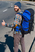 Man carrying backpack stretching thumb up — Stock Photo