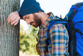 Man with backpack leaning at the tree — Stock Photo