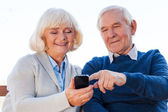 Senior couple looking at the mobile phone — Stock Photo