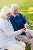 Cheerful senior couple looking at the mobile phone — Stock Photo