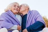 Senior man kissing his cheerful wife — Stock Photo