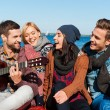 Young cheerful people sitting at the riverbank — Stock Photo #55521125